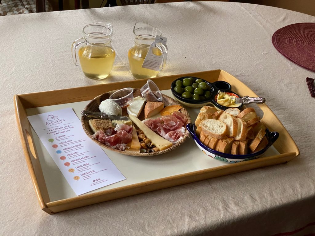 A cheese plate with wine and bread.